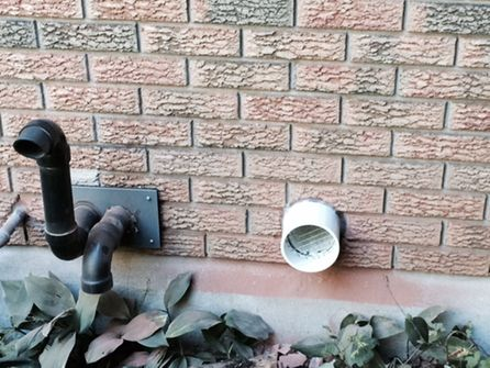 brick house exterior with pipe extruding from wall